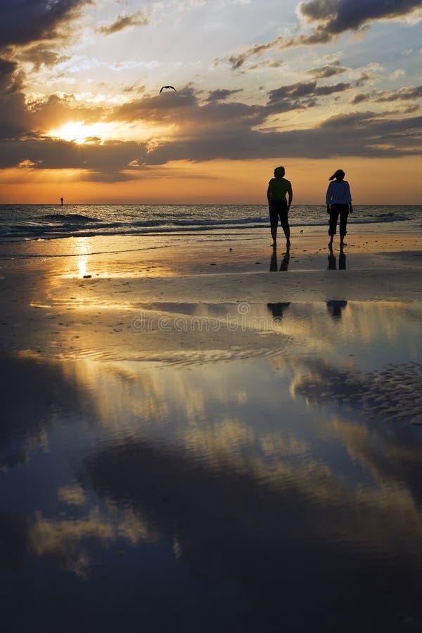 Marchant la plage au coucher du soleil image stock