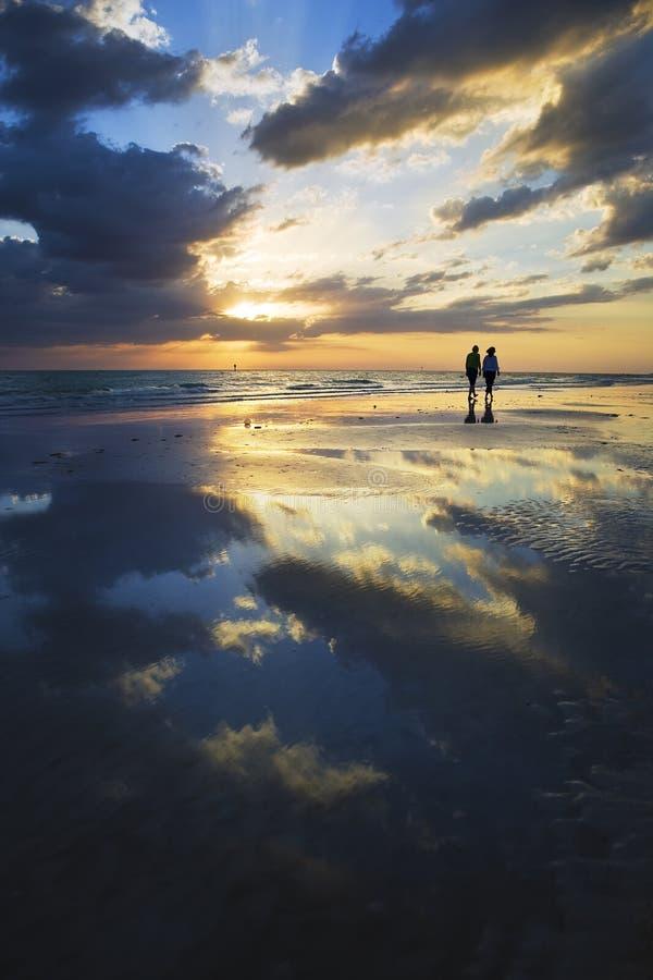 Marchant la plage au coucher du soleil image libre de droits