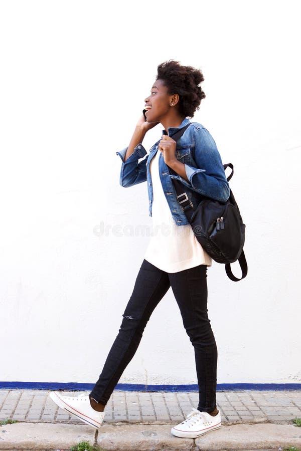 Marche à la mode de jeune femme extérieure et parler au téléphone portable image stock