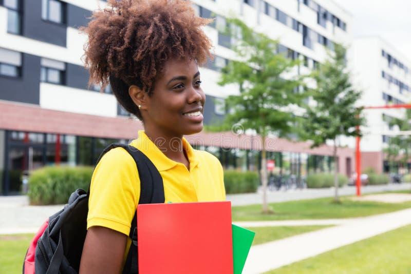 Marche d'étudiante d'afro-américain extérieure sur le campus image libre de droits