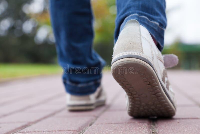 Marche dans des chaussures de sport sur le trottoir images stock