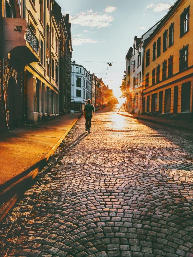 Marche de touristes d'homme dans la rue de coucher du soleil photographie stock
