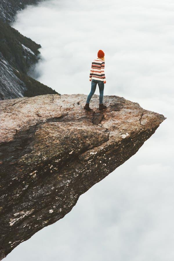 Marche de touristes de femme sur la falaise rocheuse de Trolltunga photo stock