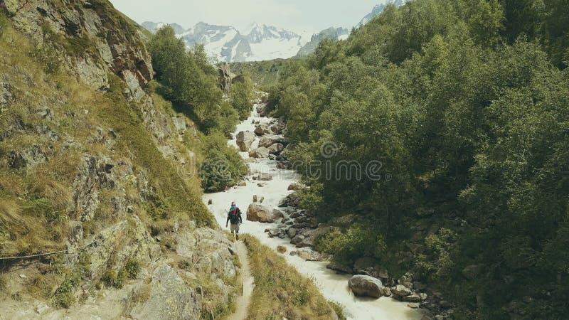 Marche de touristes de montagne le long de la vue rapide de dos de rivière Hausse de la montagne image libre de droits