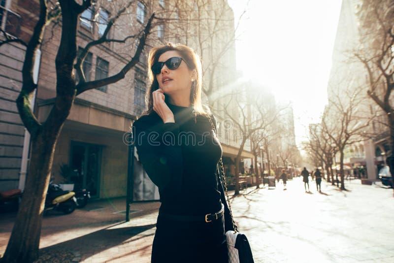 Marche femelle élégante sur la rue de ville et parler au téléphone images stock