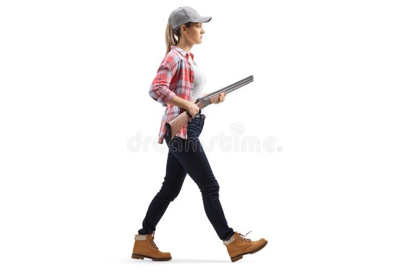 Marche femelle avec un fusil de chasse images stock