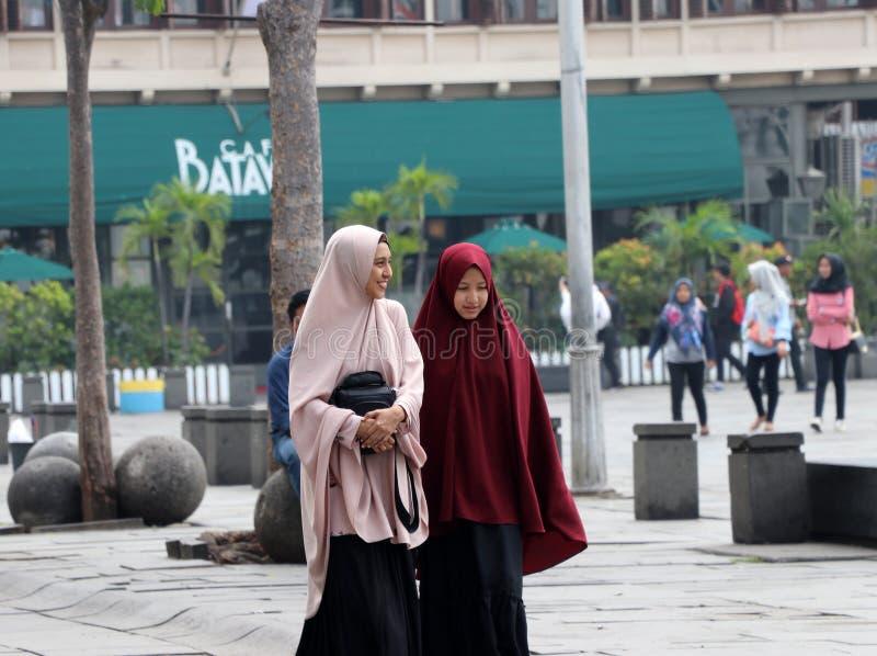 Marche indonésienne de deux femmes musulmanes dans la place de Fatahillah au vieux voisinage de ville à Jakarta photo stock