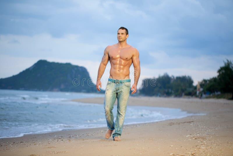 Marche mâle musculaire le long d'une plage photos stock