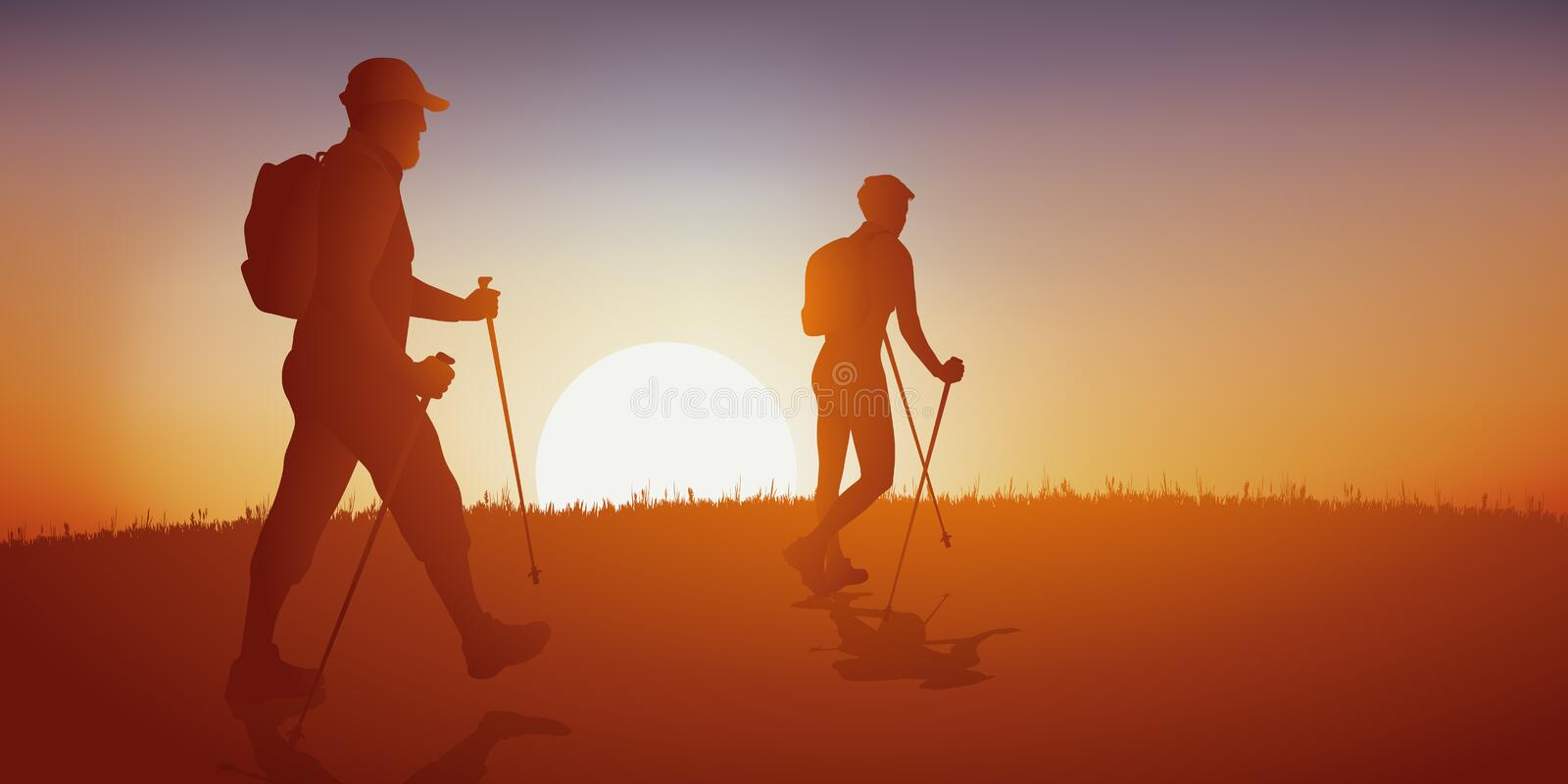 A couple of walkers go for a Nordic walk. royalty free stock image