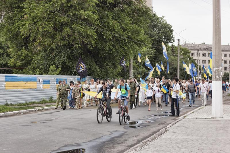 Marche solennelle des résidents de ville par les rues en l'honneur du premier anniversaire de la libération du pro-russe photo libre de droits