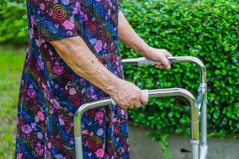 Marcheur supérieur ou plus âgé asiatique d'utilisation de vieille dame avec la santé forte tout en marchant au parc photo stock