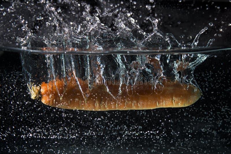 Marchewka spada wewnątrz woda zdjęcie stock