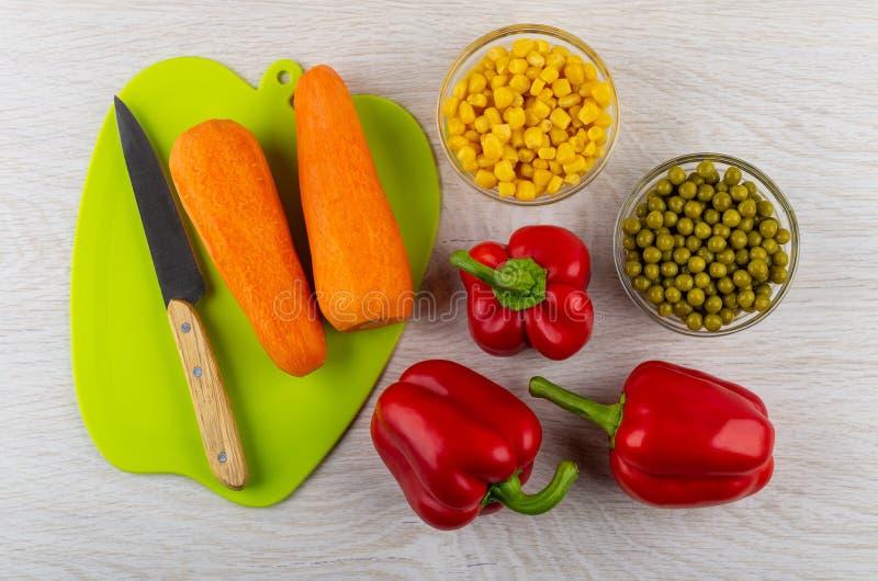 Marchewki, kuchenny nóż na tnącej desce, zieleni grochy i kukurudza w pucharach, słodcy pieprze na stole Odgórny widok obraz stock
