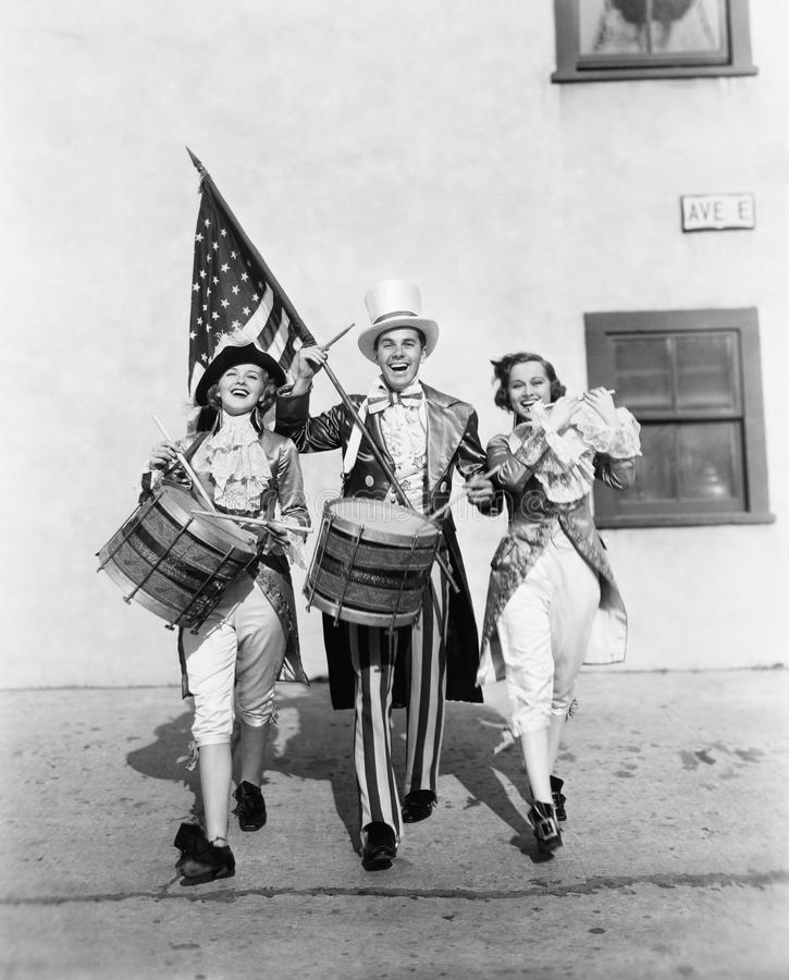 Marching band performing in a parade with an American flag. (All persons depicted are no longer living and no estate exists. Supplier grants that there will be stock images