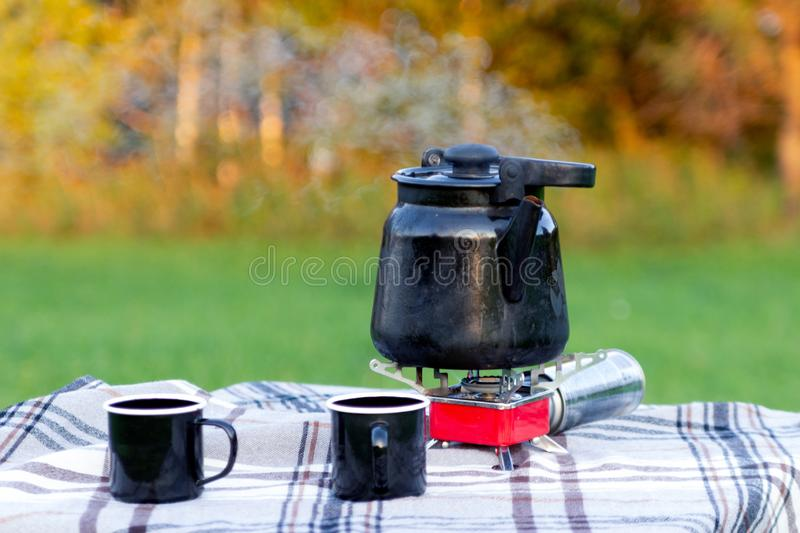 Marching hot iron black smoking teapot on red gas burner and iron mugs are standing on the table on white checkered tablecloth stock images