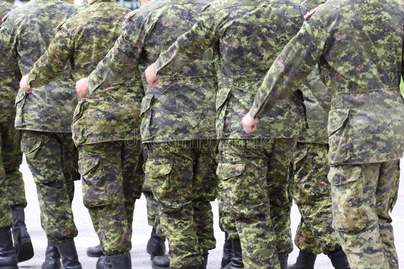 Marching soldiers in uniform. Rear side view of marching soldiers in camouflages khaki uniforms stock photography