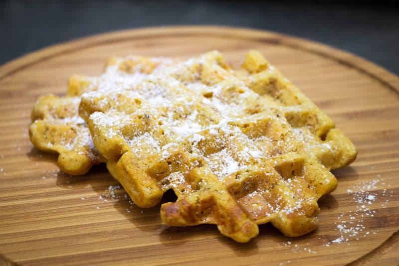 Marchwiani gofry z sproszkowanym cukierem na drewnianego boardPerfect zdrowym śniadaniu fotografia royalty free