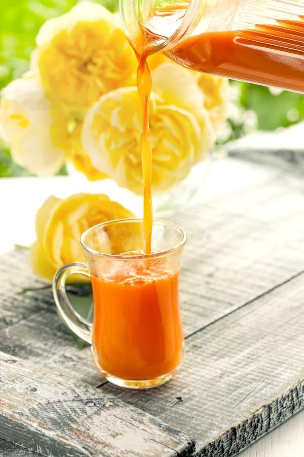 Marchwiany sok nalewa od dzbanka w szklaną filiżankę na tle róże obrazy royalty free