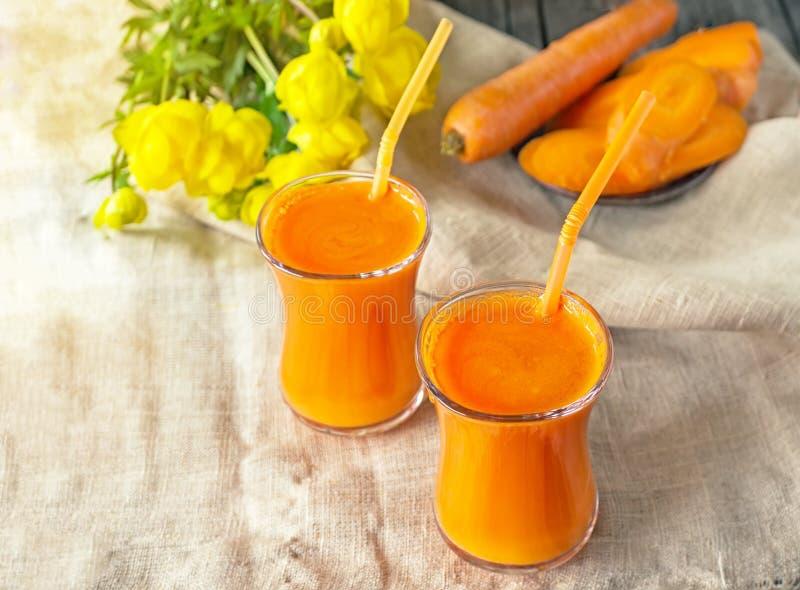 Marchwiany sok w dwa szklanej filiżanki na tle marchewki i kwiaty w wczesnym poranku zdjęcie royalty free