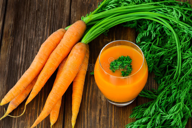 Marchwiany sok w szkle beside i warzywach fotografia royalty free