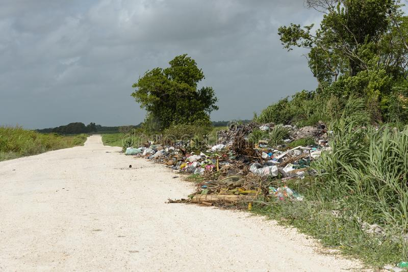 Marcia Arancione, Belize - 21 Maggio 2017: I rifiuti scaricati su strada - evidenziano il problema dello smaltimento dei rifiuti  immagine stock
