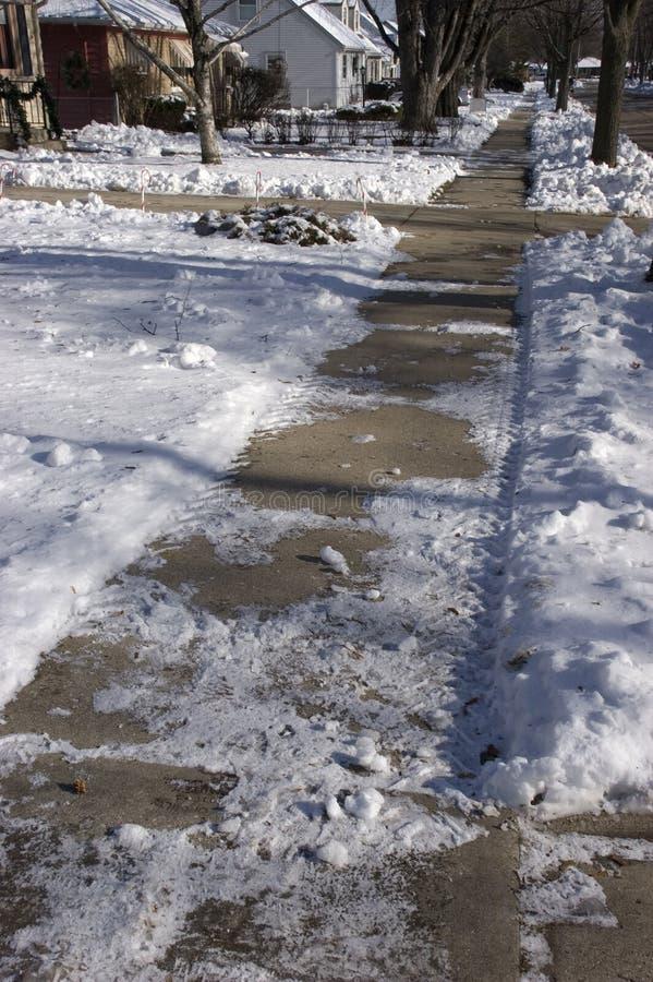 Marciapiede sdrucciolevole e ghiacciato nella città fotografie stock
