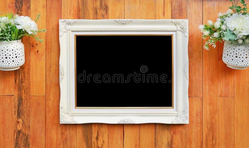 Marco blanco antiguo de la foto con el espacio vacío negro para su imagen o texto puesto en el fondo de madera de la pared del ta imagen de archivo