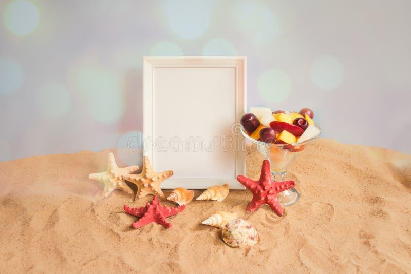 Marco blanco, cuenco de ensalada de fruta, estrellas de mar y conchas marinas en la playa de la arena en el contexto azul imagenes de archivo