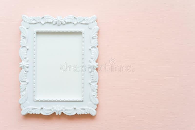 Marco blanco de la foto del vintage en el fondo de madera en colores pastel rosado plano fotos de archivo