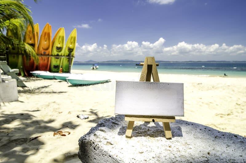 Marco blanco de la lona y trípode de madera en el fondo tropical de la playa en el día soleado imagen de archivo