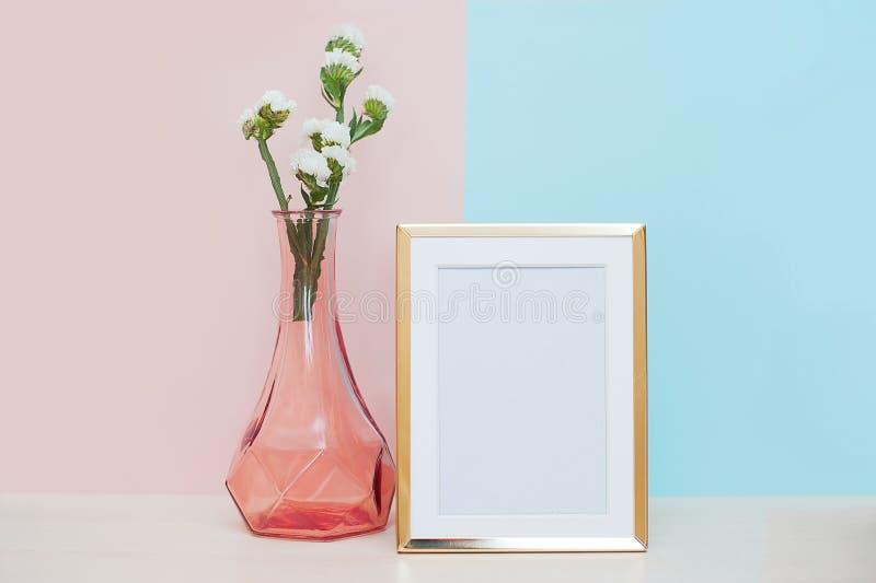 Marco blanco de oro moderno vacío de la foto contra fondo azul rosado con la flor blanca en florero rosado en la tabla moke para  foto de archivo libre de regalías