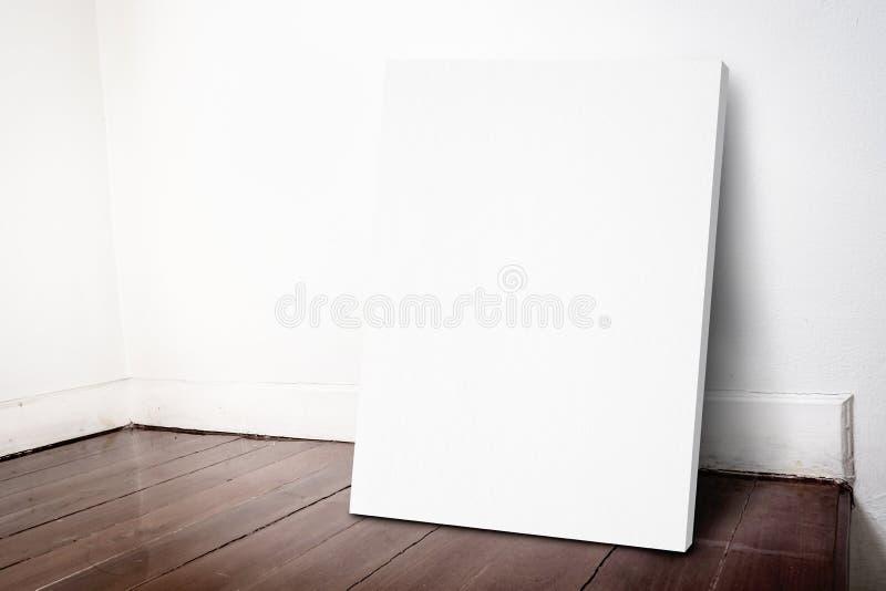 Marco blanco en blanco de la lona que se inclina en la pared de la casa del grunge y b oscuro imagen de archivo