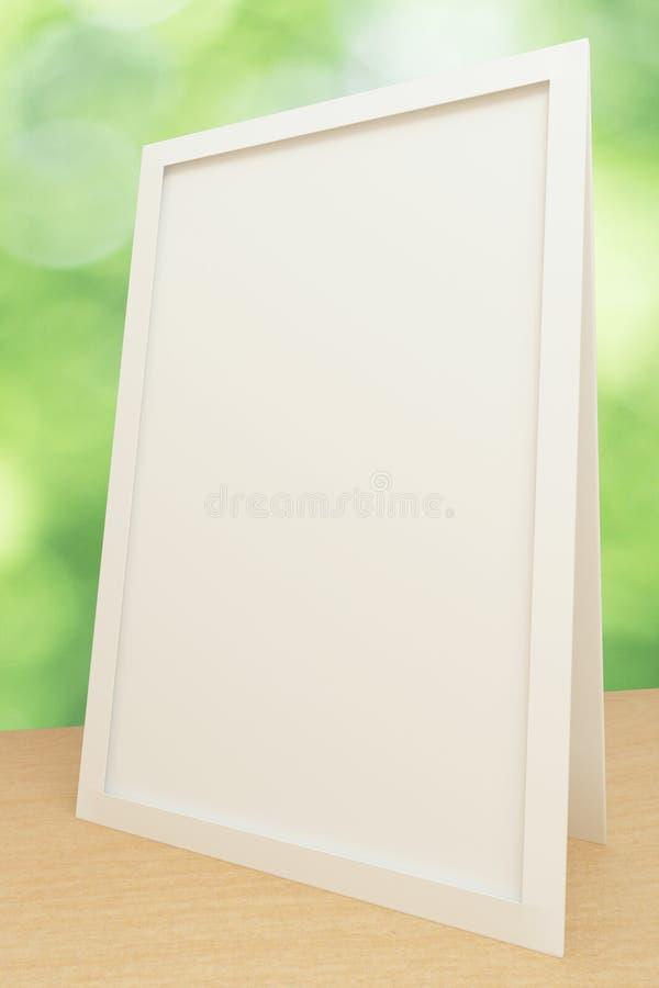 Marco blanco en blanco en la tabla de madera imagen de archivo libre de regalías