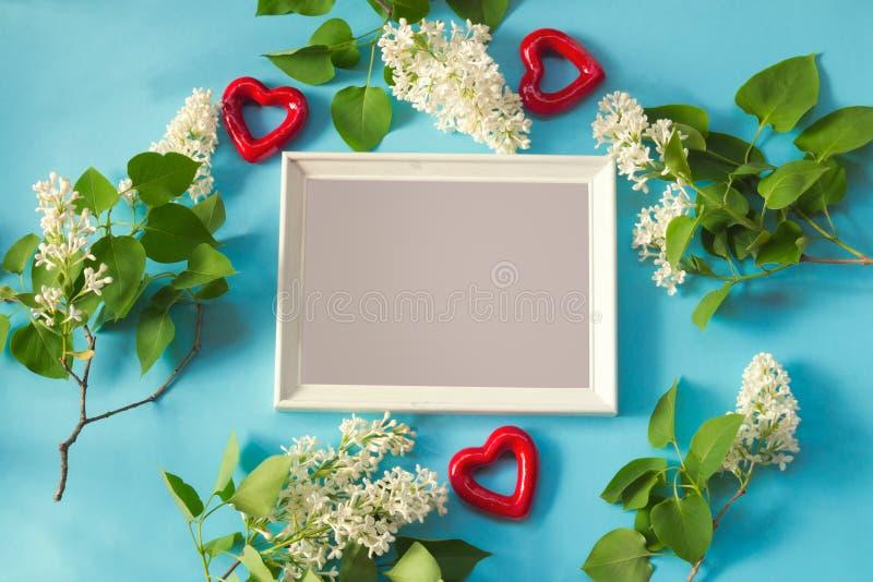 Marco blanco, flores de la lila blanca y corazones rojos en fondo azul fotos de archivo libres de regalías