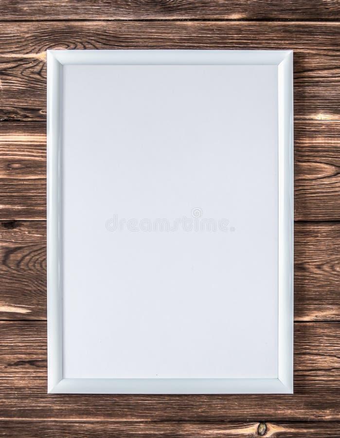 Marco blanco vacío para una imagen en un fondo marrón de madera fotos de archivo libres de regalías
