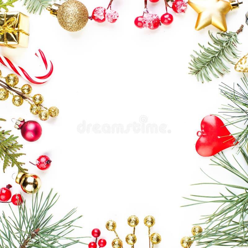 Marco colorido de la Navidad con la decoración del rojo y del oro y la ramita verde del árbol de Navidad en el fondo blanco foto de archivo libre de regalías