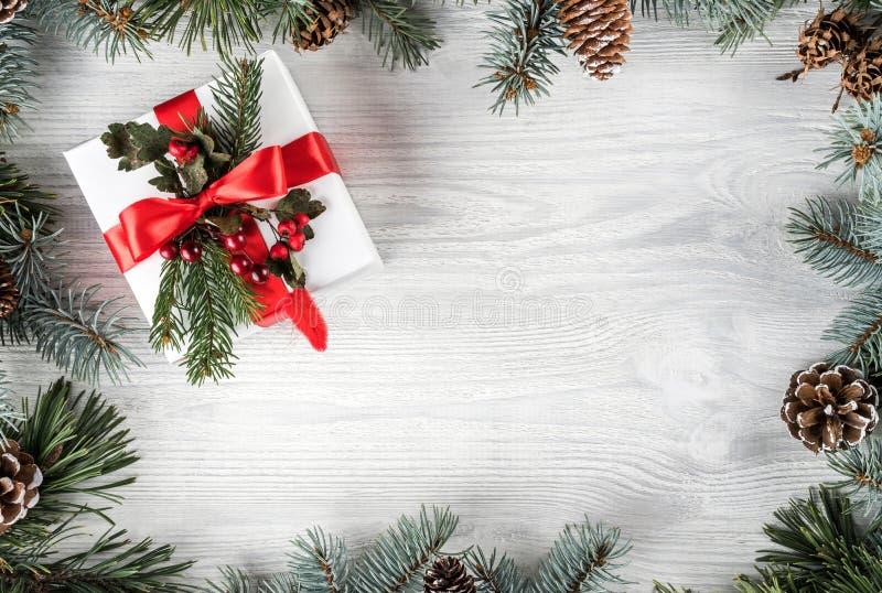 Marco creativo hecho de ramas del abeto de la Navidad en el fondo de madera blanco con la caja de regalo, conos del pino Tema de  fotos de archivo