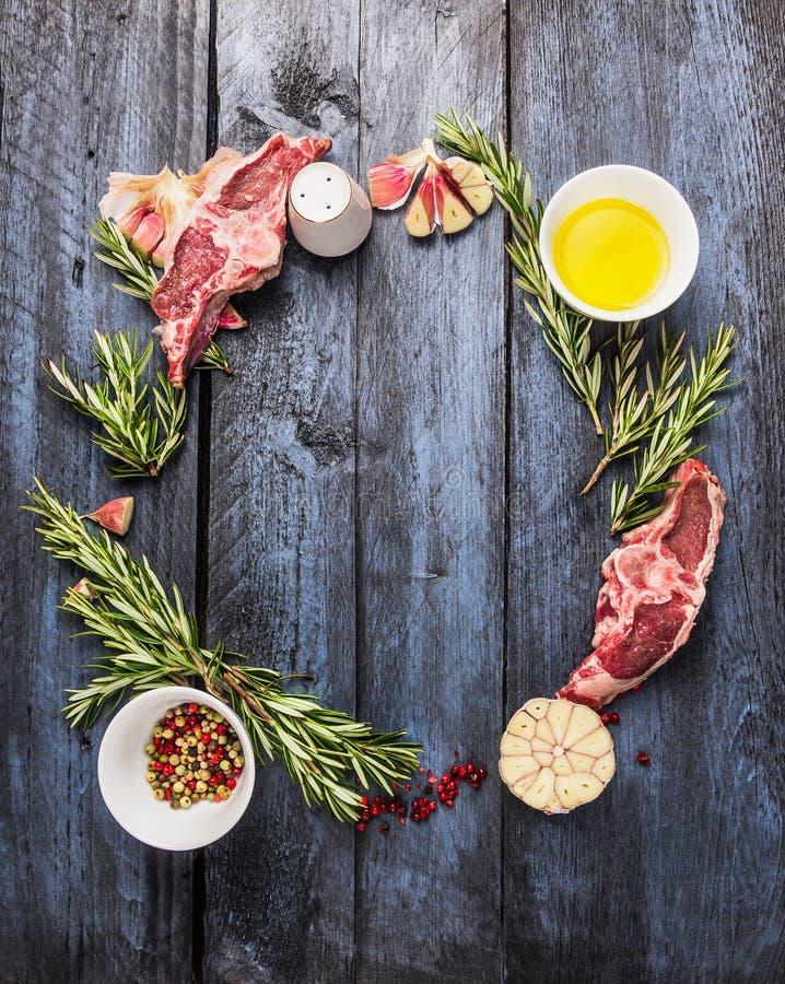Marco crudo del círculo de la carne del cordero con las hierbas del romero, ajo y aceite, en fondo de madera azul imagenes de archivo