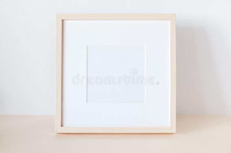Marco cuadrado de madera con la maqueta del cartel foto de archivo
