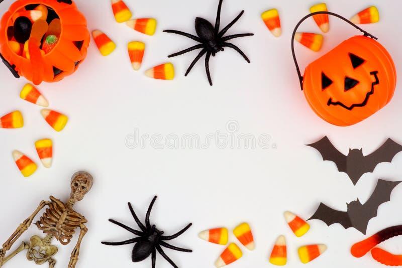 Marco de Halloween del caramelo y de la decoración dispersados sobre blanco imagen de archivo