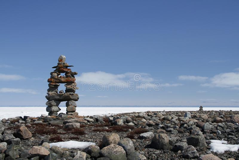 Marco de Inuksuk com a baía congelada no fundo foto de stock royalty free