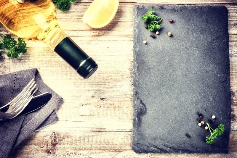 Marco de la cena con la botella de vino blanco y de cubiertos en etiqueta de madera foto de archivo libre de regalías