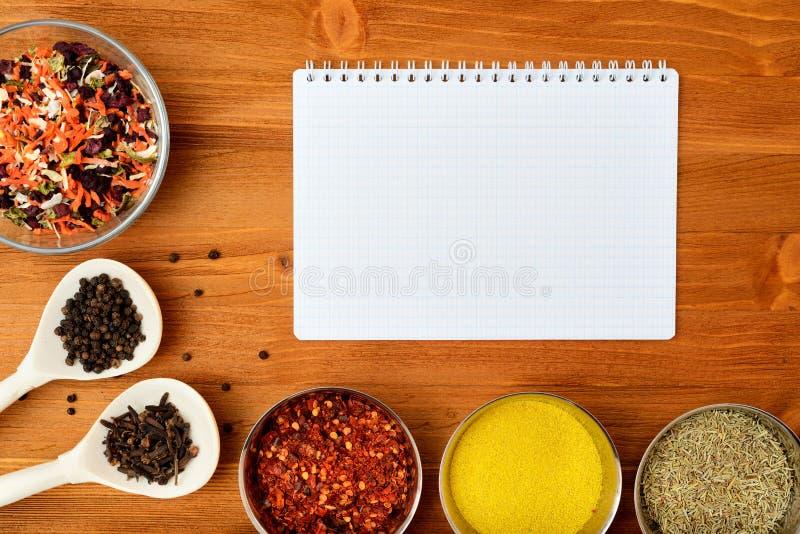 Marco de la comida de Copyspace con las especias del papel de la libreta y los accesorios el cocinar foto de archivo