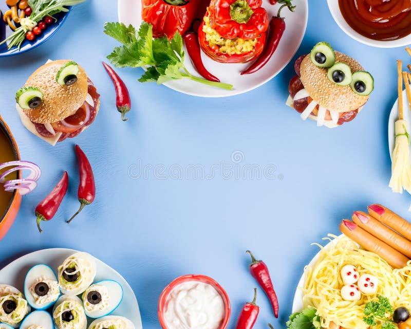 Marco de la comida del partido de Halloween Pimientas rellenas con las caras asustadizas, escobas de brujas del queso, hamburgues foto de archivo