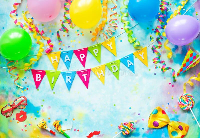Marco de la fiesta de cumpleaños con los globos, las flámulas y el confeti en fondo colorido con el espacio de la copia fotos de archivo