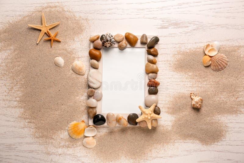 Marco de la foto adornado con los guijarros y las cáscaras del mar en el fondo de madera blanco imagen de archivo libre de regalías