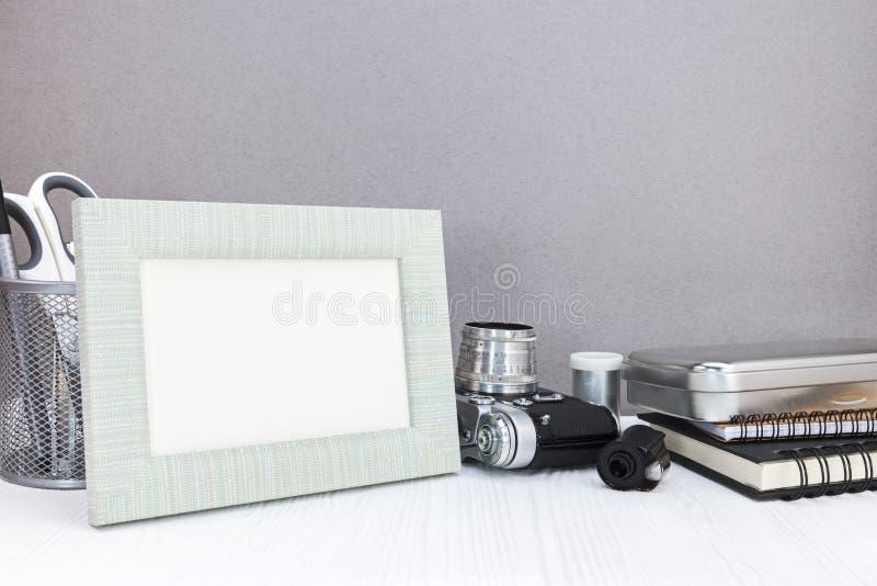 Marco de la foto, cámara del vintage, inmóvil, cuadernos en el tabl blanco fotografía de archivo