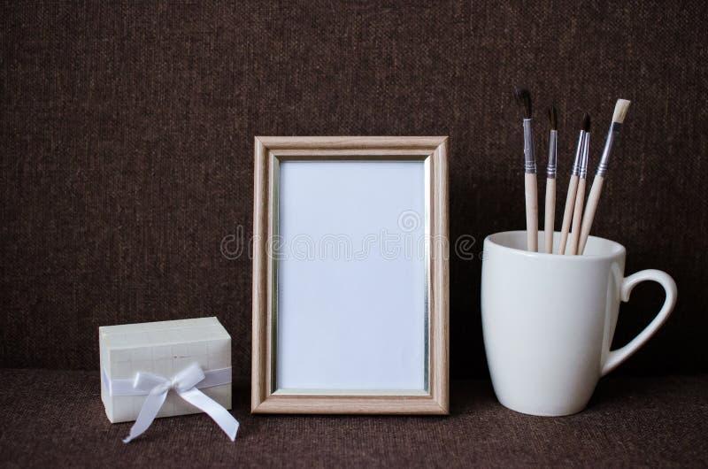 Marco de la foto, cepillo en una taza y una caja imagen de archivo libre de regalías