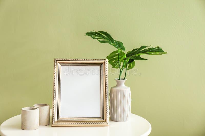 Marco de la foto con las hojas en florero y candeleros en la tabla blanca contra fondo del color foto de archivo libre de regalías