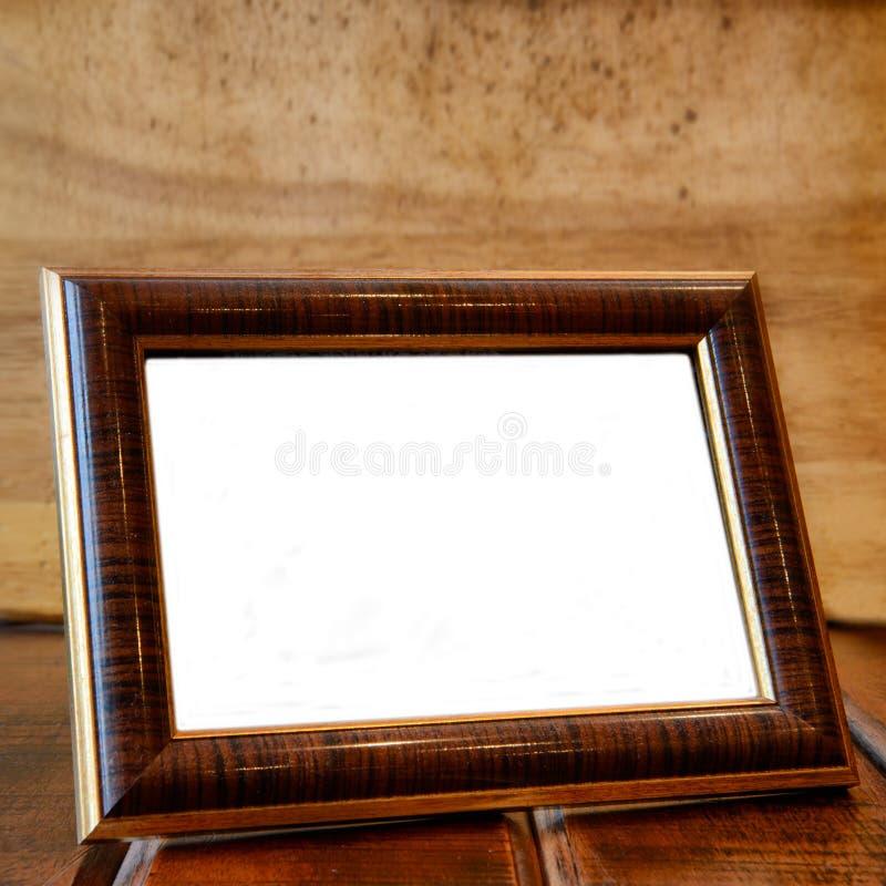 Marco de la foto en el escritorio de madera imagenes de archivo